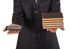 Businessman's hands offering choice between obsolete books or sm Stock Images