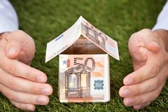 Businessman's Hands Protecting Euro House On Grassy Land Royalty Free Stock Photography