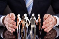 Businessman's hands protecting team of paper people on desk Royalty Free Stock Images