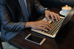 Businessman`s hands typing on laptop keyboard at workplace. stock photo
