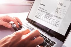 Businessman`s Hands Working On Invoice On Laptop stock images