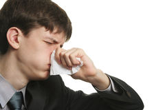 Businessman's illness. Ill young man with sad eyes and kleenex on his nose Royalty Free Stock Photos