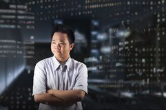 Businessman`s Office Crossed Arms Concept. A young business man wearing white shirt crossed arms and thinking about something while standing near the office Stock Photo