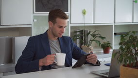 Businessman about 30s reading on the touch screen tablet. Caucasian man sitting at the contemporary office wearing in blue jacket and grey t-shirt. Professional stock video footage