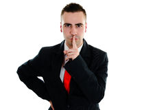 Businessman's secret. Businessman holds a finger to his lips, saying It's a secret Stock Photos
