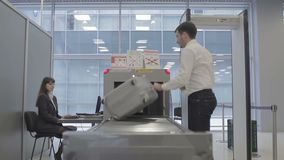 Businessman`s suitcase goes through the x-ray scanner. Handsome businessman is in the security check room in the airport. Cute airport worker looks at the stock video footage