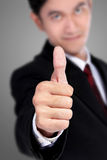 Businessman's thumb up focus, on grey background Royalty Free Stock Photos