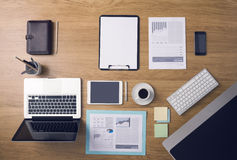 Businessman's tidy desktop. And work tools with paperwork, computer, touch screen devices and stationery on a wooden surface, top view Stock Image