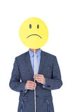 Businessman with sad smiley faced balloon at office desk Stock Image