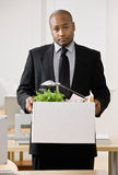 Businessman sadly packing personal desk items Royalty Free Stock Images