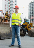 Businessman in safety jacket and hardhat posing next to bulldoze Stock Image