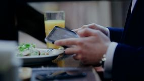 Businessman with salad and working on a tablet. Businessman drinking coffee and reading news in cafe stock video footage
