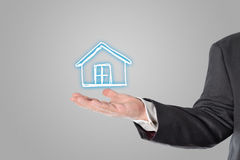Businessman, salesman, house symbol in the hand
