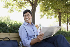 Businessman With Sandwich And Newspaper Sitting On Bench Royalty Free Stock Image