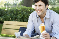 Businessman With Sandwich And Newspaper Sitting On Bench At Park Royalty Free Stock Photo