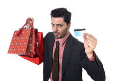 Businessman in Santa Claus Christmas hat holding sopping bags and credit card in worried and stress. Young attractive business holding shopping bags and credit royalty free stock photography