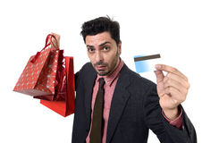 Businessman in Santa Claus Christmas hat holding sopping bags and credit card in worried and stress. Young attractive business holding shopping bags and credit royalty free stock photos