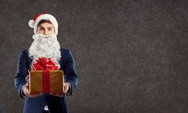 Businessman in Santa Claus costume with a gift in his hand. Royalty Free Stock Photo