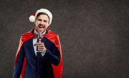 Businessman in Santa Claus costume superhero sing song.  royalty free stock photo