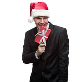 Businessman in santa hat biting gift Royalty Free Stock Photo
