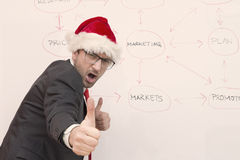 Businessman with Santa hat expressing satisfaction showing his thumbs up. Happy businessman showing his thumbs up as a symbol of success. He is wearing Santa Stock Image