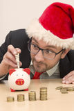 Businessman with Santa hat inserting one dollar bill into piggy bank Royalty Free Stock Images