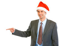 Businessman in Santa hat pointing at copy space Royalty Free Stock Image