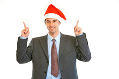 Businessman in Santa hat pointing at copy space Royalty Free Stock Photos