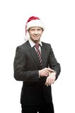 Businessman in santa hat pointing at watch Stock Photography