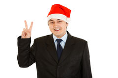 Businessman in Santa hat showing victory gesture Stock Image