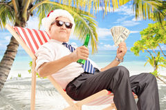 Businessman with santa hat sitting on chair and holding dollars. Smiling businessman with santa hat sitting on a beach chair and holding dollars and beer, on a Royalty Free Stock Images
