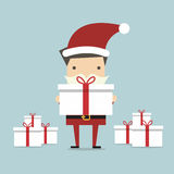 Businessman Santa holding a big gift box Stock Images