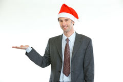 Businessman in Santas hat presenting something Stock Image