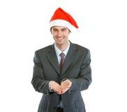 Businessman in Santas hat presenting something Stock Photos