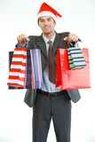 Businessman in Santas hat showing shopping bags Royalty Free Stock Images