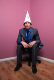 Businessman sat in corner wearing dunce hat Royalty Free Stock Images