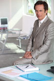 Businessman sat on table Stock Photos