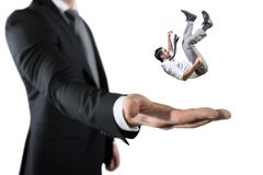 Businessman is saved from a big hand. Concept of business support and assistance royalty free stock photo