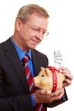 Businessman saving Euro banknotes. Smiling senior businessman holding piggy bank and banknotes Royalty Free Stock Images