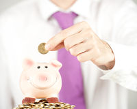 Businessman saving money Stock Images