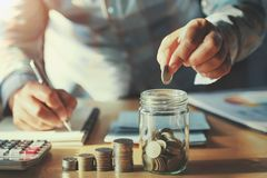 Businessman saving money concept. hand holding coins putting in. Jug glass royalty free stock photos