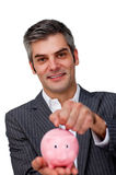 Businessman saving money in a piggy-bank Royalty Free Stock Images