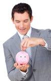 Businessman saving money in a piggy-bank Stock Photo