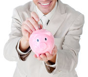 Businessman saving money in a piggy-bank Stock Images