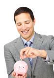 Businessman saving money in a piggy-bank Royalty Free Stock Photography
