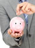 Businessman saving money in a piggy-bank Royalty Free Stock Photo