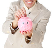 Businessman saving money in a piggy-bank Royalty Free Stock Photo