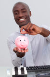 Businessman saving money in a piggybank. Happy Afro-American businessman saving money in a piggybank in the office Stock Images