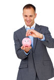 Businessman saving money in a piggybank. Charismatic businessman saving money in a piggybank against a white background Stock Photography