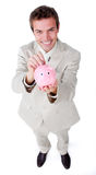 Businessman saving money in a piggybank Royalty Free Stock Photos